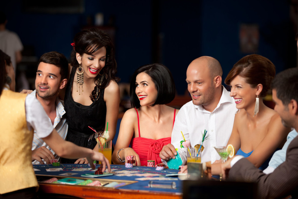 laughing friends playing cards in a casino